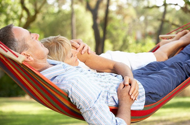 A couple resting in a hammock. Financial freedom will allow you to enjoy more time like that.