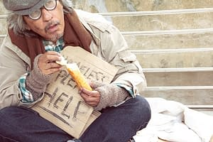 Homeless man begging and eating bread.