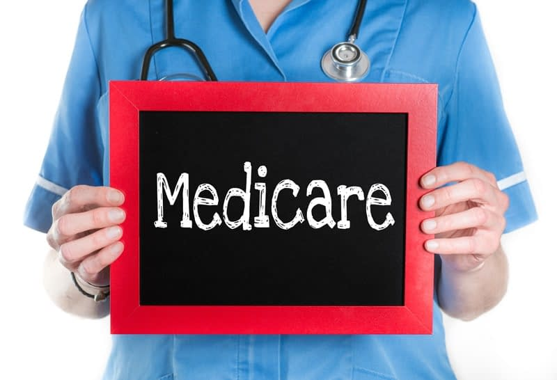 Medicare Benefits represented by a health care worker holding a Medicare sign.