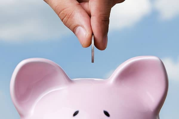When it comes to saving for college save money as seen here with a coin in the piggy bank.