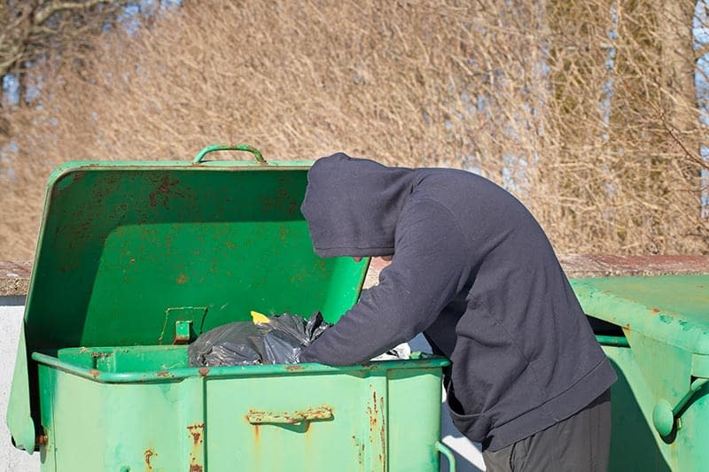 Homeless man dumpster diving for food since he ran out of money in retirement.